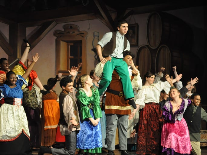Gaston's friend Lafou (Ryan Capal, center) tries to cheer up his friend after Belle turns down his marriage proposal. Shown in the tavern are villagers Morgan Strupe, Tyuan Anderson, Azia Thompson, Nadia Goforth, Alex Huckleberry, Celeste Hackmann, Lisa Grub, Ryan Capal (Lafou), Adrian Rankin (Gaston), Lena Kohler, Allison Holtman and Josh Hall.