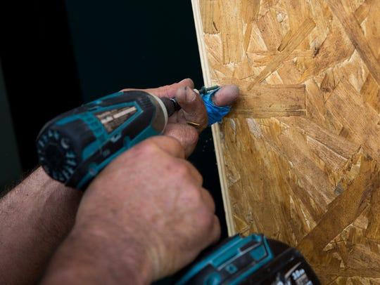 Alberto Trabaglianti screws in plywood boards to protect