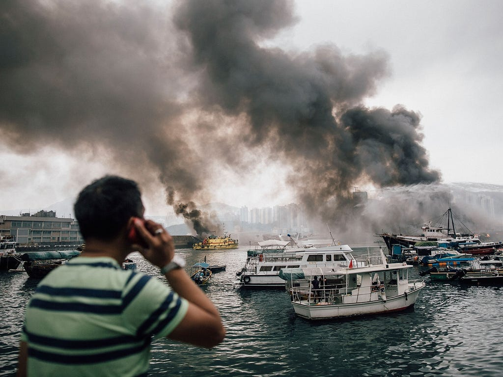 Residents and bystanders watch as firefighters extinguish fires on boats at the Shau Kei Wan typhoon shelter on in Hong Kong. A fire swept through several boats anchored at the Shau Kei Wan typhoon shelter.
