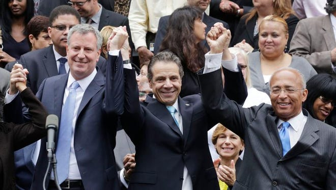 New York Gov. Andrew Cuomo, center, raises the hands of Democratic mayoral candidates Bill de Blasio, left, and Bill Thompson on the steps of City Hall on  Monday, Sept. 16, 2013 in New York. Thompson conceded to de Blasio, avoiding a runoff election in the Democratic primary, leaving de Blasio to face Republican candidate Joe Lhota in the Nov. 5 election.