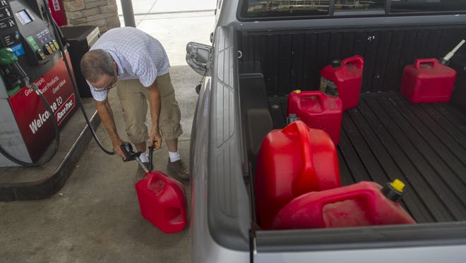 In this file photo, Hector Diaz of Miami fills up gas cans in Fort Myers to go back to Miami to be with his wife during Hurricane Matthew.