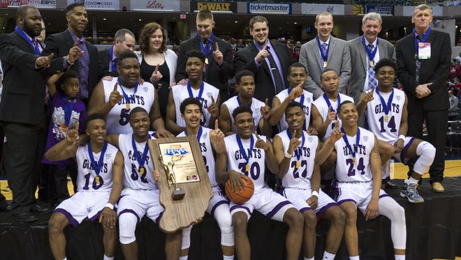 FILE -- The Ben Davis High School Giants celebrate with their trophy after winning the IHSAA 2017 Class 4A State Championship Game at Banker's Life Fieldhouse in Indianapolis, Saturday, March 25, 2017. Ben Davis won 55-52.