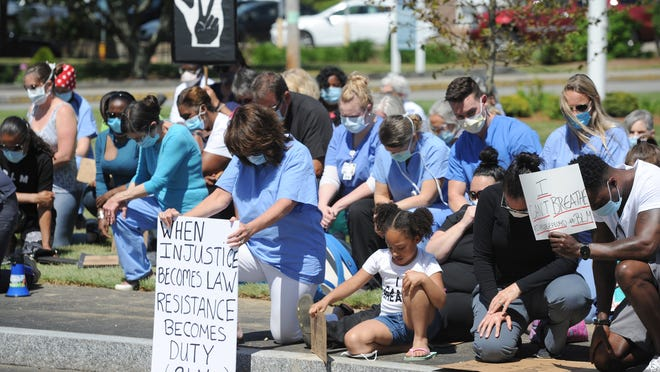 With her sign, Mary Ellen Nelson, an occupational therapist at Cape Cod Hospital, center, kneels with others Monday. Cape Cod Healthcare employees joined others for a Black Lives Matter kneel-down event in front of Cape Cod Hospital. To see more photos, go to www.capecodtimes.com/photos.