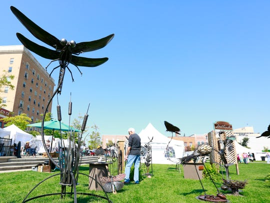 A large dragonfly metal sculpture displays for sale