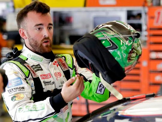 Austin Dillon prepares his helmet before a NASCAR auto