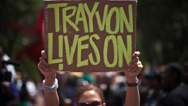 A woman holds a sign as she attends a rally honoring Trayvon Martin organized by the National Action Network outside One Police Plaza in Manhattan on July 20, 2013