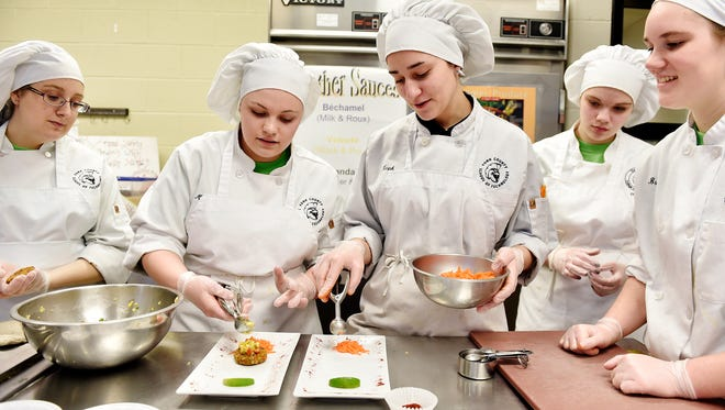 York Tech juniors Mary Parrigan, second from left, and Ellen Murphy, center, work to plate lentil-barley burgers with fruit salsa as teammates Nicole Shemberger, far left; Heather Koterwas, second from right; and Brooke Glass, far right, watch. The school is participating in NASA's Hunch (High School Students United with NASA to Create Hardware) program, which enables students to design and create products for use in the International Space Station. York Tech is one of 30 schools participating in HUNCH's culinary competition, for which a team of 6 York Tech students developed a recipe meeting nutritional and other standards set by NASA.