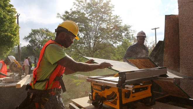 Trevon Blanding ,20,  of Detroit uses a table saw to cut plywood to board-up and secure the abandoned former DPS Greenfield Park Elementary School in Detroit on Friday, September 25, 2015. City of Detroit has created Opportunity Detroit Youth Board-up, in collaboration with Jenkins Construction,  Building Trades Unions, and Detroit Employment Solutions to help young adults learn trade skills to be able to join the work force that is driving the rebuilding of the city of Detroit.