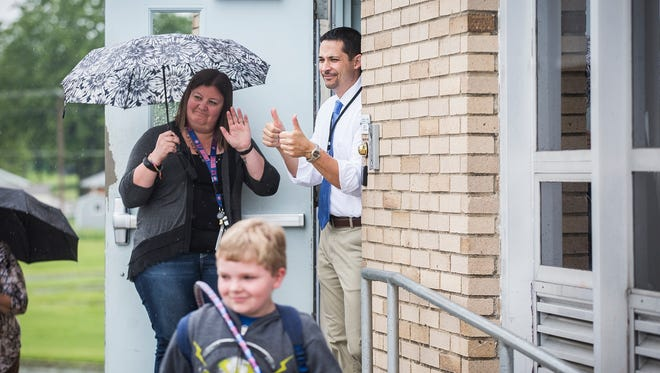 Principal Eric Ambler gives thumbs up as the last student exits Storer Elementary School on the last day of school Wednesday, May 24, 2017.