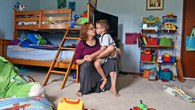 Trish Kisielnicki holds her son Sean, 7, as he undergoes his weekly enzyme replacement infusion in his Hopewell Township bedroom Wednesday, July 12, 2017. Sean, 7, is the second-youngest of six children in his tight-knit family, who live on eight acres with a large garden and a menagerie of animals. Sean has Hunter syndrome — a terminal genetic enzyme deficiency that affects 400-500 people in the U.S. and that, for Sean, brings an array of accompanying conditions such as autism, attention deficit hyperactivity disorder and sensory processing disorder.