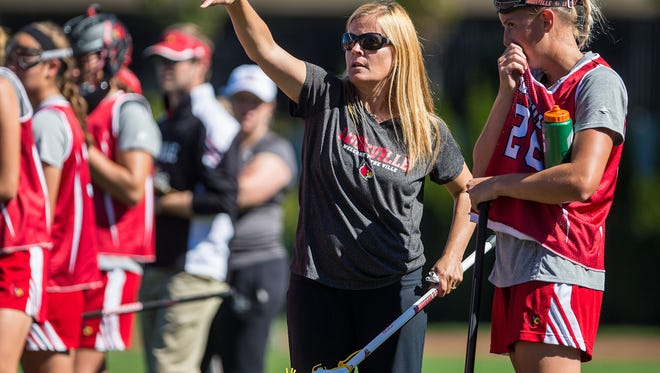 09/28/2013  BOSTON, MA    University of Louisville head coach Kellie Young (center) spoke with team member Colleen O'Malley (right) during a women's lacrosse game between the University of Louisville and Boston University held at Nickerson Field in Boston. Louisville won the game 13-5.  (Photo by Aram Boghosian)
