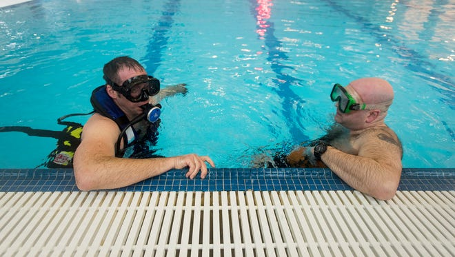 Port Huron firefighter Steve Didocha, right, gives direction to firefighter Roger Howison during water rescue training at the YMCA pool in Port Huron Monday, Feb. 20.