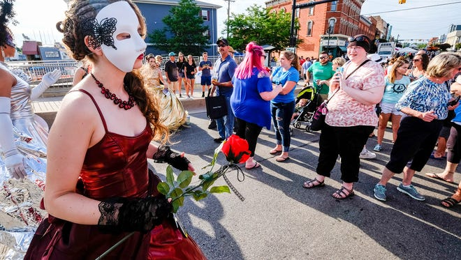 Human mannequins from Salon PiZazz! pose on Huron Avenue to raise money for a nonprofit on Family Night Thursday, July 12, 2018, during Boat Week in Port Huron.