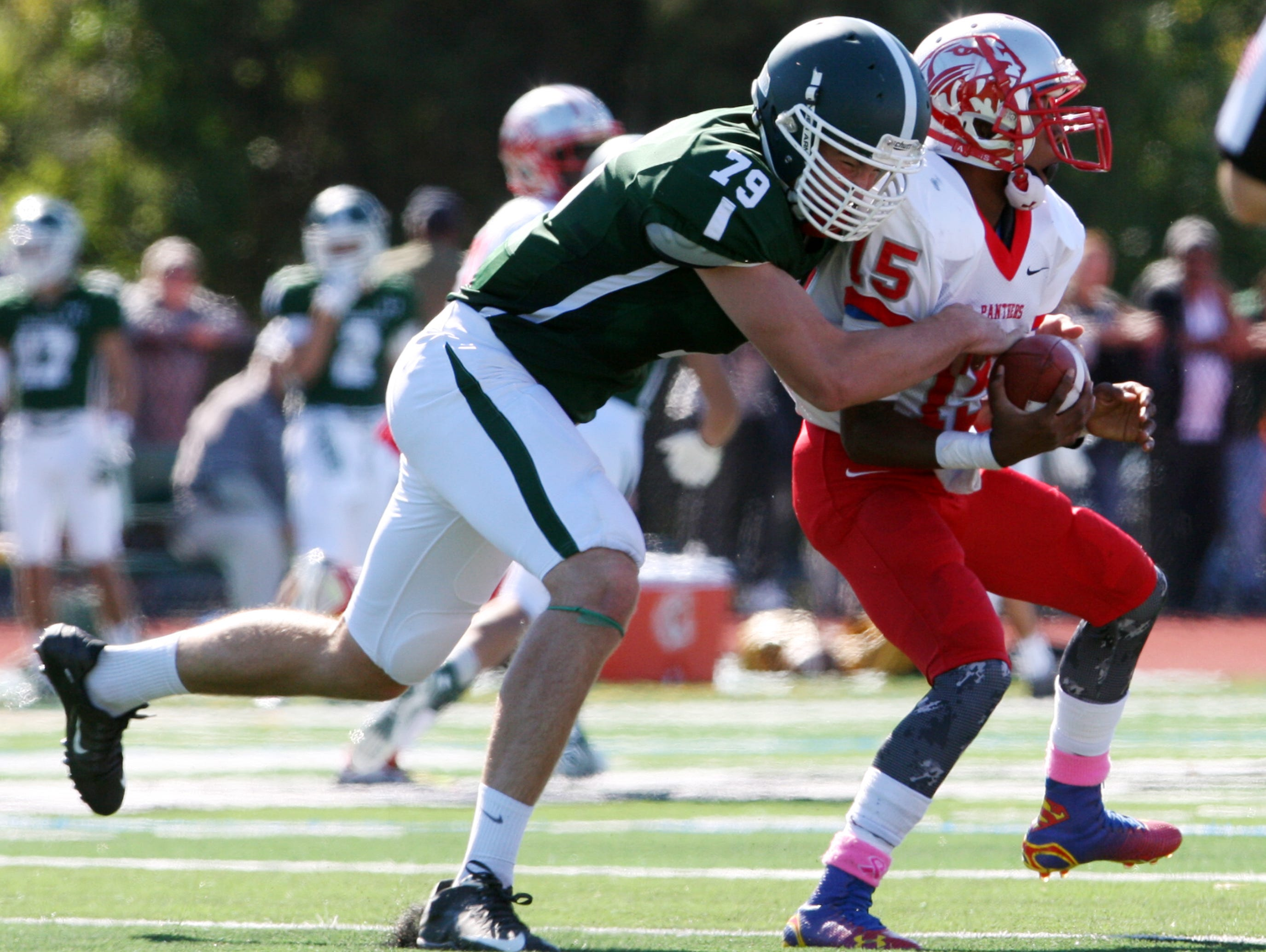 Action photos from the Perth Amboy High School at St. Joseph football game held at St. Joseph's new turf field in Metuhen on Saturday October 10, 2015. Here St. Joseph's # 79 (left)- Bryan Carley sacks Perth Amboy quarterback # 15 (right) Tahjmere Oneal.