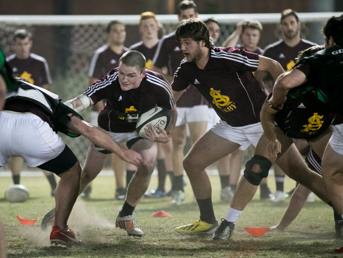 ASU's Tommy Boyle breaks through some tackles during an ASU Rugby team practice in Tempe, AZ on Thursday, April 3, 2014.