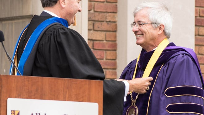 J. Donald Sheets, chairman of Albion College's Board of Trustees, hangs a medallion around the neck of Mauri Ditzler, Albion College's new president, during inauguration ceremonies conducted Friday.  Al Lassen/For the Enquirer Donald Sheets, chair of Albion College's Board of Trustees hangs a medallion around Mauri Ditzler, Albion College's new president during inauguration ceremonies on Friday.  Al Lassen/For the Enquirer