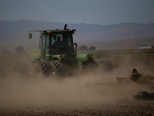 A tractor kicks up dust as it drives through an unplanted