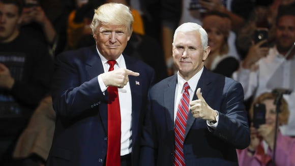 President-elect Donald Trump and Vice President-elect Mike Pence acknowledge the crowd in Cincinnati during the first stop of Trump's post-election tour on Dec. 1, 2016.