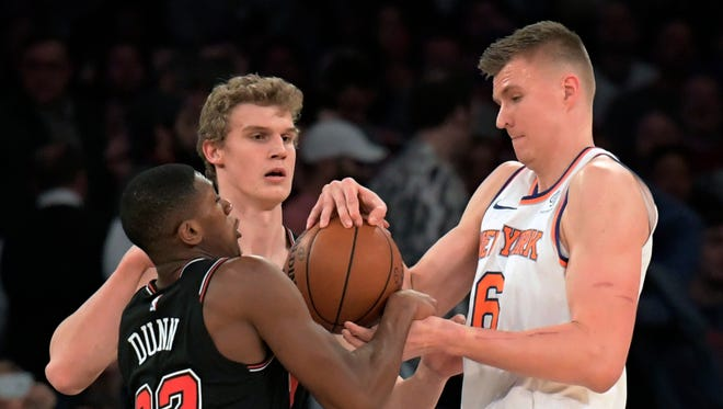 New York Knicks forward Kristaps Porzingis (6) fights for the ball with Chicago Bulls guard Kris Dunn (32) during the first quarter of an NBA basketball game Wednesday, Jan. 10, 2018, at Madison Square Garden in New York.