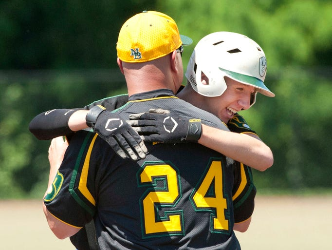 North Bullitt Eagles' Ryan Henson hugs 1st base coach Chris Kelly after driving in the winning run of the game in the top of the 6th inning. The Eagles beat Butler 3-2 to win the Region 6 championship game.  31 May 2014