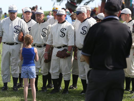 A young girl asks for a picture with the Ghost Players at the Field of Dreams movie site on Saturday, June 14, 2014, outside Dyersville, Iowa.