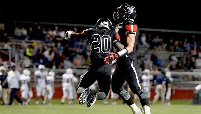 St. Johns running back Steven Linton, left, and quarterback Blake Thelen, right, celebrate after Linton dove into the endzone for what turned out to be the winning score against East Lansing late in St. Johns Friday August 28, 2015. St. Johns tacked on another score after this one.