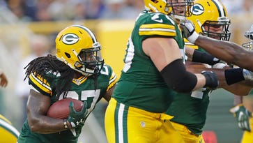Green Bay Packers running back Eddie Lacy runs behind the block of guard T.J. Lang (70) during a preseason game against the Oakland Raiders at Lambeau Field in August.