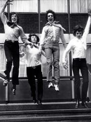 Members of the psychedelic rock band Pink Floyd leap