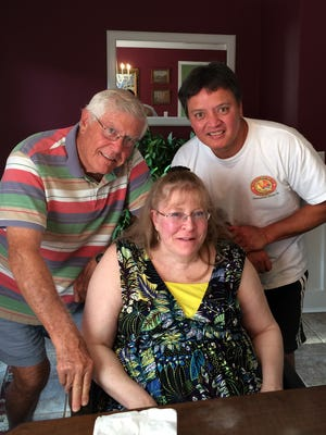 Terry Paulino of Arkansas (center), who was paralyzed during spine surgery performed by doctor Cyril Raben, is shown with her husband, Eddie (right), and her father, Mike Renuart.