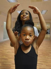 Sherricka Jones helps Ziyhanna Martin with her arm