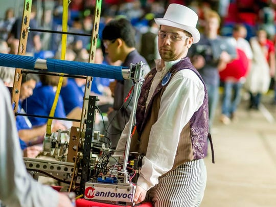 Mentor Nate Remaker carries team STEMpunk's robot to the competition space just before a match during the world championship.