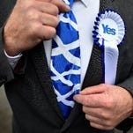 A pro-independence supporter wearing a tie with the Scottish flag poses for a picture outside a polling station in Strichen, Aberdeenshire, on September 18, 2014, during Scotland's independence referendum.
