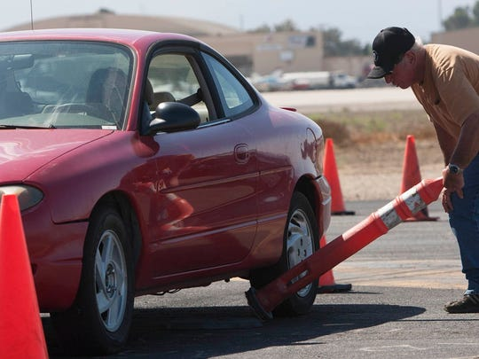 In this 2013 photo, instructor Jim Wilkey picks up a cone at the Camarillo Airport after one of his stunt driving students knocked it over sliding into it.