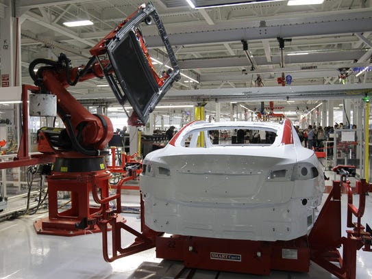 A robot puts on the top of a Tesla Model S at the Tesla