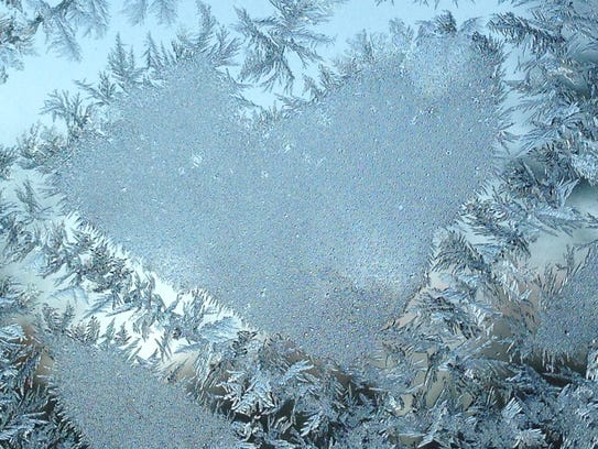 Frost on a window forms a heart-shaped pattern on Feb.