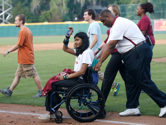 """Farham """"Ronny"""" Ahmed waves to the crowd at the FSU baseball field on Friday while being pushed by FSU Chief of Police David Perry after a ceremony, which recognized the victims and first responders from last fall's Strozier Library shooting."""