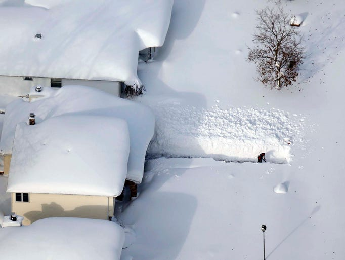 A man digs out his driveway in Depew, N.Y.,Wednesday,