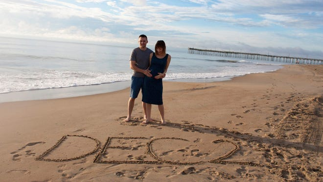 Ashley May and her husband, Curtis, announced their due date with this photo taken at Virginia Beach.