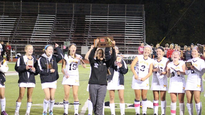 West Milford veteran field hockey coach Krista Provost hoists the Passaic County championship trophy last fall after her Highlanders defeated Pompton Lakes in the title game. Provost was recently named overall Passaic County Coach of the Year.