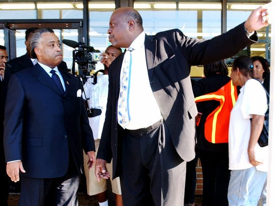 -  -Dr. Artis Cash, right, shows the Rev. Al Sharpton
