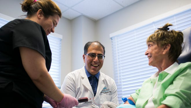 Dr. Farhan Taghizadeh of Arizona Facial Plastics works with nurse Sarah Porter (left) to draw blood from patient Jill McKnight at his business in Phoenix on July 11, 2018. McKnight was at Arizona Facial Plastics for a hair rejuvenation procedure.