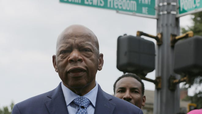 U.S. Rep. John Lewis stands in front of John Lewis Freedom Parkway moments after its new name was unveiled in Atlanta, Wednesday, Aug. 22, 2018. Atlanta is honoring Lewis by renaming a street after the civil rights icon.