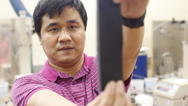Dr. Changchun Zeng, co-inventor of Auxetic Foam from the FAMU-FSU College of Engineering, holds a piece of the material at the school's Materials Institute on Tuesday. The foam actually increases in size when stretched or pressed.