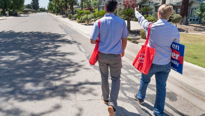 Volunteers Hector Agredano, left, and Kyle Lyons canvass homes on Monday, May 7, 2018 in the 3700 block of West Damsen Avenue to garner support for California Assembly candidate Warren Gubler.