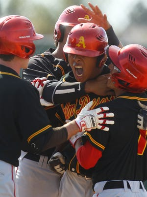 Palm Desert High School's Jeremiah Estrada is embraced at home by his team mates after hitting a three run home run to take the lead in the sixth inning during their quarterfinal game against Edison High School (Huntington Beach). Palm Desert won 3-2 and advances to the semifinals.