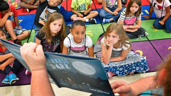 Students listen to a story being read by Paula Hodge