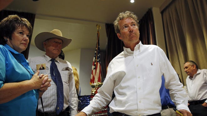 Republican presidential candidate Sen. Rand Paul, R-Ky., right, during a political event Monday in Mesquite, Nev. Carol Bundy, left, and Cliven Bundy, in cowboy hat, stand nearby.