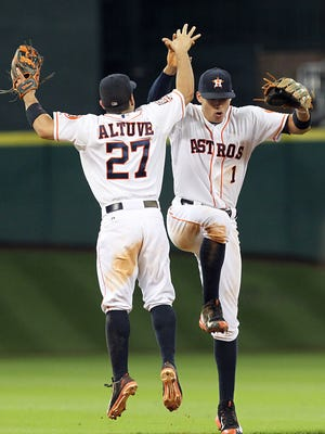 Houston Astros second baseman Jose Altuve (27) and  shortstop Carlos Correa (1) celebrate their victory over the Los Angeles Angels at Minute Maid Park.