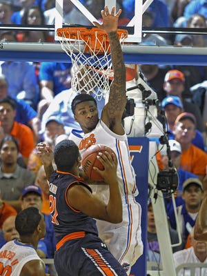 Florida's Chris Walker (23) goes high to block a shot by Auburn guard Malcolm Canada (21) during the first half of an NCAA college basketball game Wednesday Feb. 19, 2014 in Gainesville.
