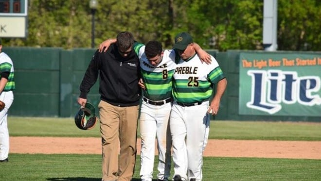 Green Bay Preble's Griffin Summers is helped off the field after breaking his left leg during a May 25 game.
